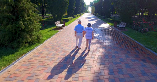 Aerial footage of senior couple walking outdoors in park Footage