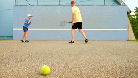 Father and son practice tennis at training wall. Hobby players with racket and b Footage
