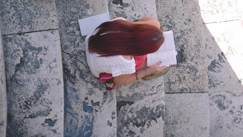 Girl reading a book on marble stairs, high-angle shot, Italy Live Action