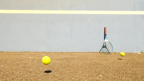 Empty training tennis court with blue bouncing tennis wall. Old yellow ball is j Footage
