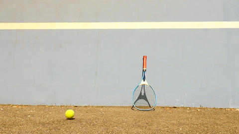 Empty training tennis court with blue bouncing tennis wall. Old yellow ball is j Filmmaterial