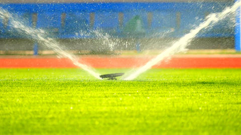 Watering the football field by underground sprinklers. Lawn grass on the footbal Footage