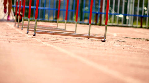 Sportswoman practicing hurdle race on the athletic ground, hard athletic trainin Live Action