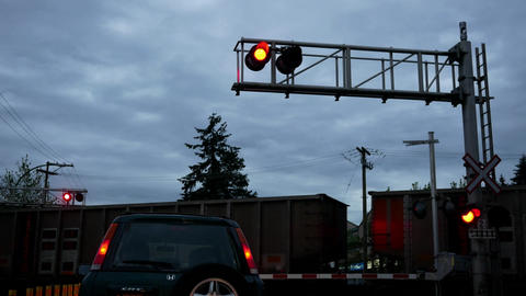 Motion of car stopped at railway level crossing barriers and flashing lights for Footage