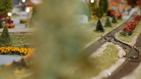 Model train passing behind a tree on a diorama Footage