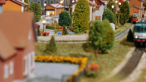 Model trains transit and a tram departs on a diorama Footage