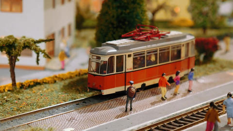 Model trains transit and a tram departs on a diorama, close up Footage