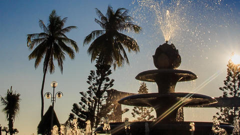 upper jet of round cascade fountain sprays in tropical park Footage