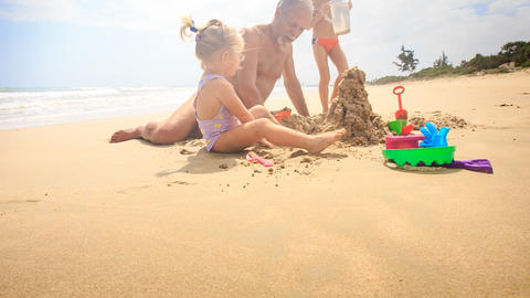 Grandpa Kids Build Sand Castle on Beach by Wave Surf Footage