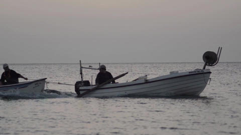 Fisherman is boat towing another boat in the early hours of the morning heading  Footage