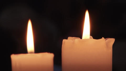 Two white candles, thick burning. The first candle is melted by the flame, has a Footage