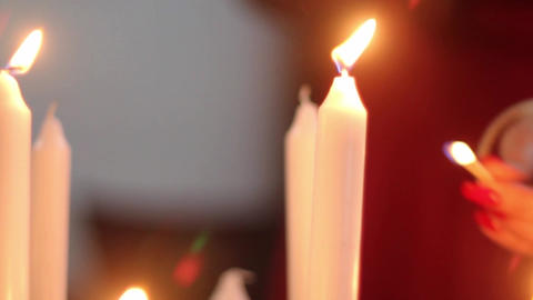 Woman lights a matchstick a candle placed in a candlestick on the table 3 Footage