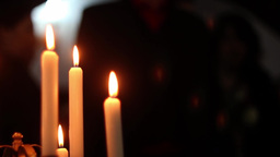 Candles burning while some silhouettes of people are seen approaching 4 Footage