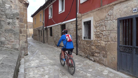 group of cyclists crossing a narrow street between the houses one storey 16 Footage