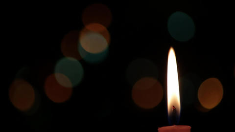 Candle with black background that is seen Christmas lights 4 Footage