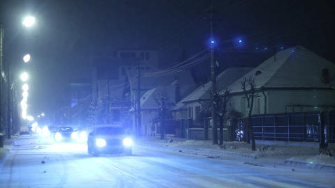 One winter evening when it was snowing outside cars passing on the street 2 Footage