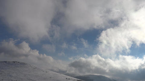 Fluffy white clouds moving over blue sky The hills are covered with snow 75 Footage