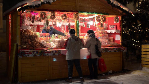 Two people buy sweets from a kiosk located in the central square, the time Chris Footage