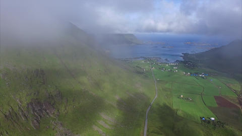 Flying in the clouds above green farmland on Lofoten Footage