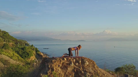 Drone Approaches Girl Doing Exercises on Steep Cliff in Morning Footage