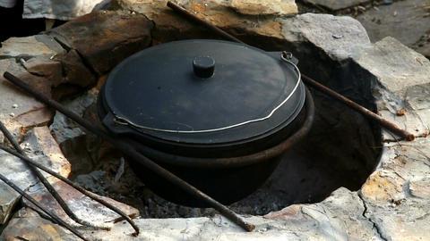 Uzbek national dish pilaf in a large cast-iron cauldron on the fire Image