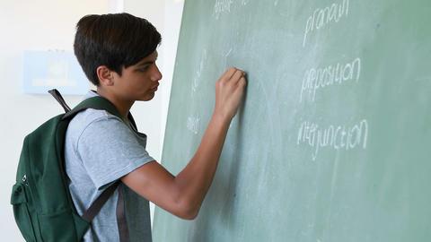 Schoolboy writing on green chalkboard in classroom Footage
