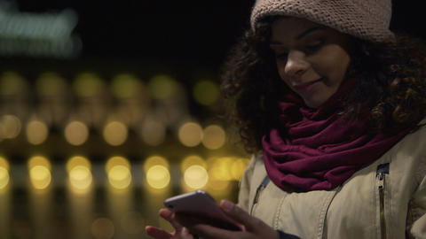 Beautiful girl reading romantic love correspondence on her cellphone and smiling Footage