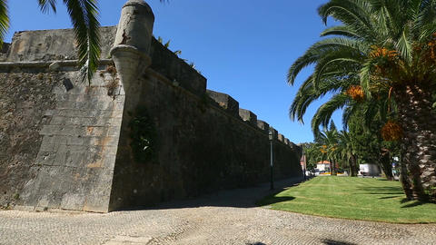 Old high fortifying wall in city with sidewalk along it, panorama and sequence Footage