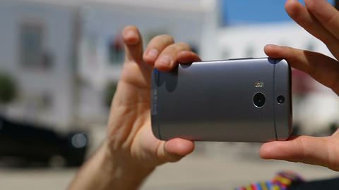 Man holding cell phone horizontally, taking panorama shot at place of interest Footage