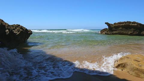 Choppy ocean rolling foamy waves onto golden coast in tiny bay between two rocks Footage