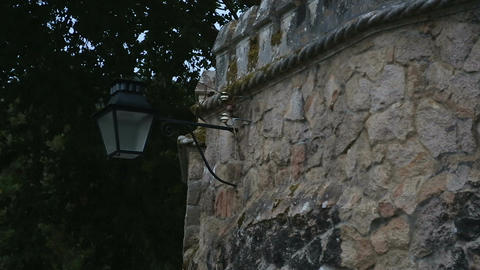 Street lamp hanging on high stone wall and beautifully designed arch over window Footage
