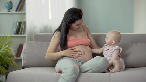 Future mother waiting for birth of baby, cute child touching pregnant belly Footage