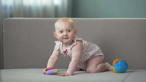 Healthy baby jumping on sofa, playing with colorful toys, enjoying happy life Footage