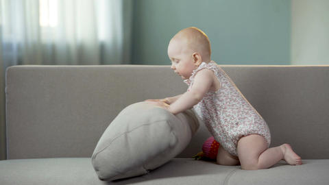 Playful baby girl having fun on sofa at home, active infant discovering world Footage