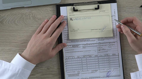 Male doctor checking his medicine prescription and signing health insurance form Footage