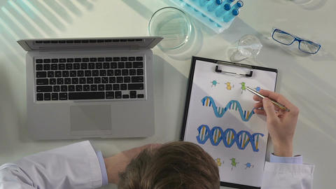 Laboratory worker studying structure of human DNA double helix, making notes Footage