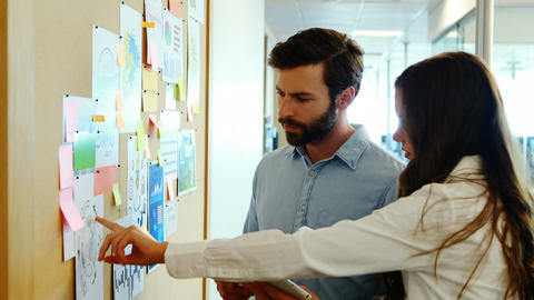 Business colleagues discussing over sticky notes Live Action