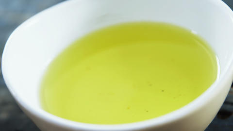 Piece of bread falling in olive oil Footage