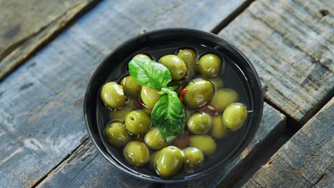 Bowl of green olives in vinegar garnished with herb Footage