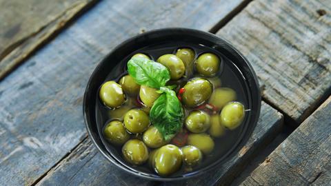 Bowl of green olives in vinegar garnished with herb Live Action