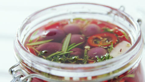 Pickled olives and herbs in a jar Live Action