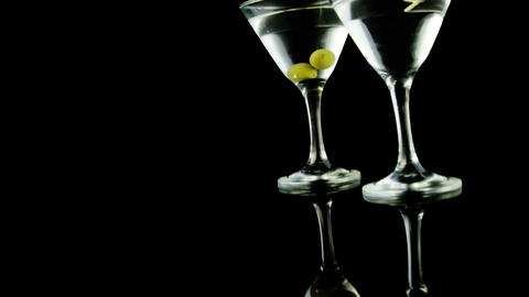 Two cocktail glasses garnished with green olives Footage