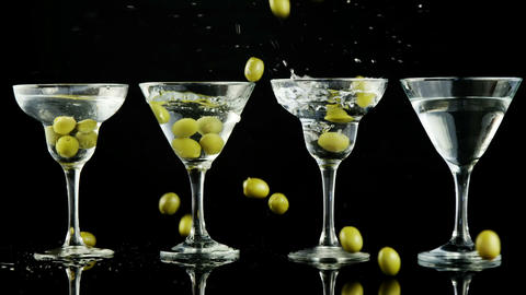 Green olives being dropped into four cocktail glasses Footage