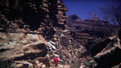 1972: Man hiking dry desert mountain trail with red backpack to river bed Footage