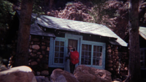 1972: Man entering small rural cabin with hiking backpack on Footage