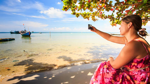 Blond Girl Sits on Beach Takes Photo of Boats in Azure Sea Footage