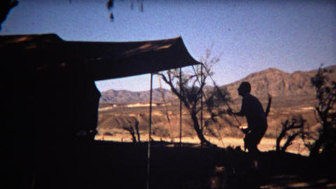 1972: Man setting up camping tent silhouette with beautiful mountain background Footage