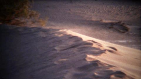 1972: Dust blowing off top of sanddune on windy sunny day Footage