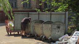 Beggar homeless man digging in trash Footage