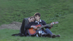 A guy and a girl on a romantic date sitting on the grass in a Park in spring Footage